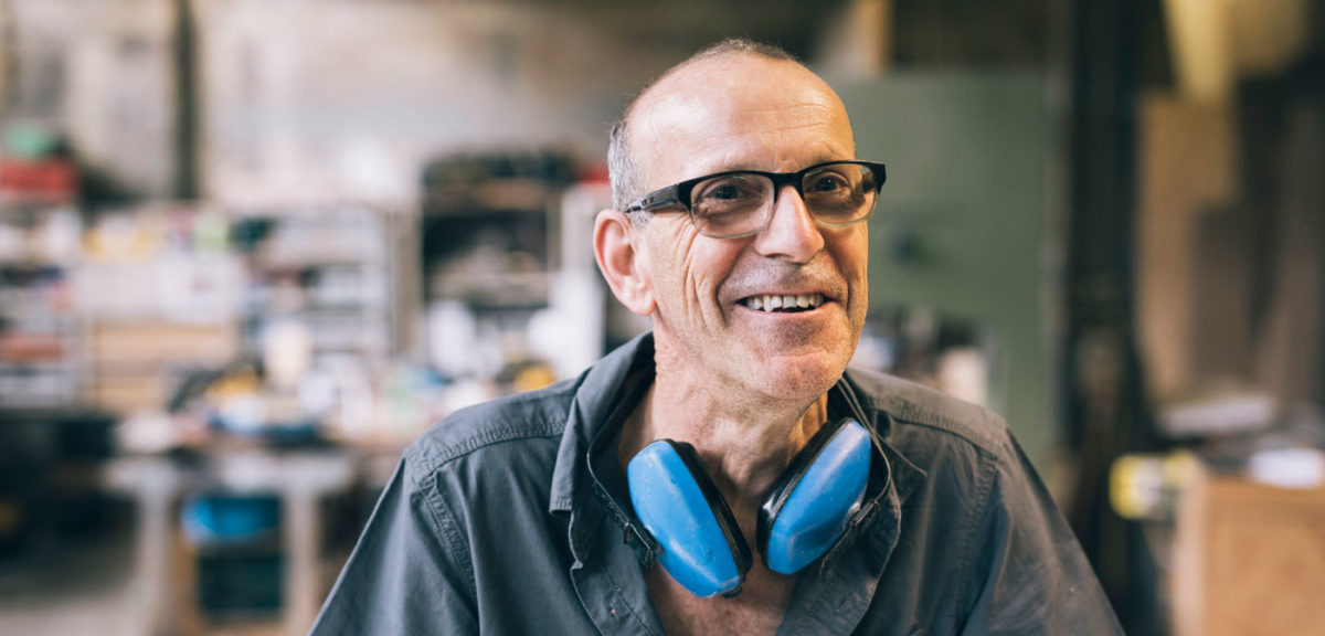 older adult with glasses smiles while he works