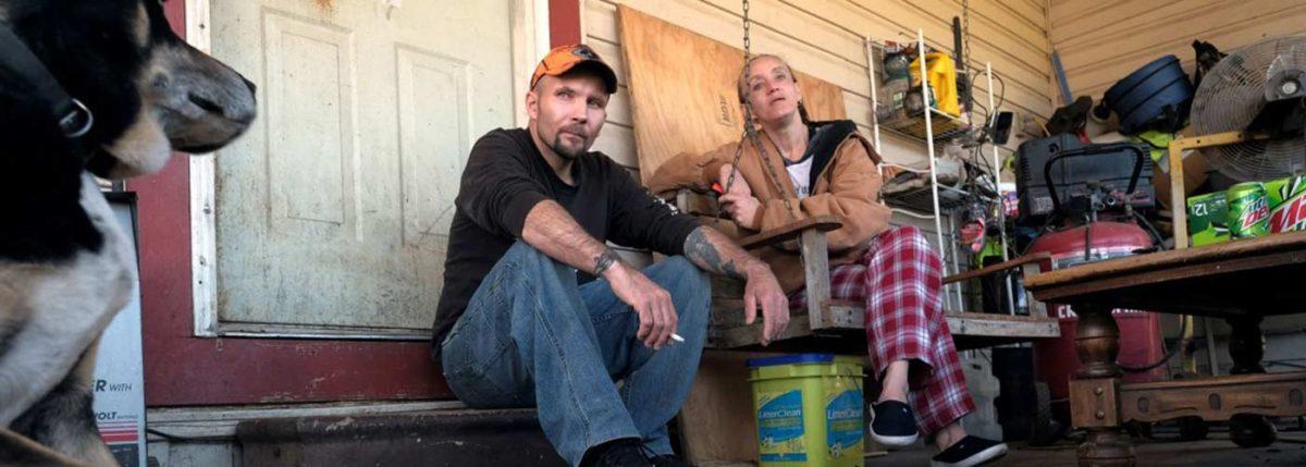 rural americans sitting on door frame