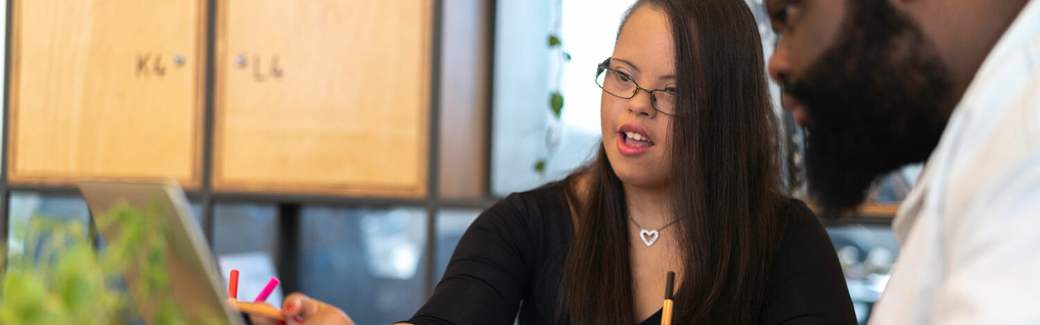 Young business woman with a disability working with a colleague