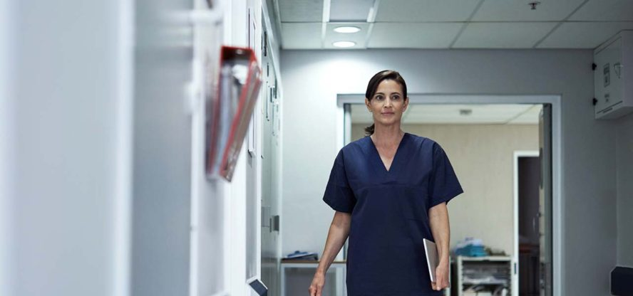 nurse walks on hallways seems worried about her employment protections