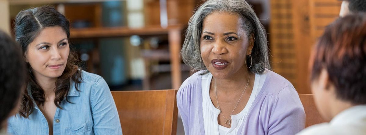 psychological practice - African american Psychiatrist communicating with group