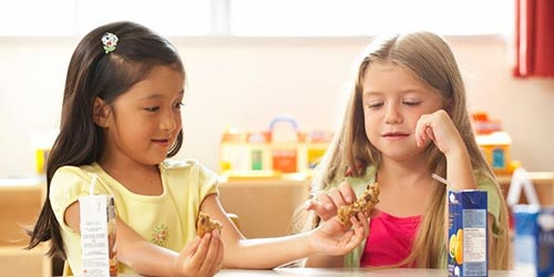 Dark haired and blond girl share a chocolate chip cooke in kinder garden classroom