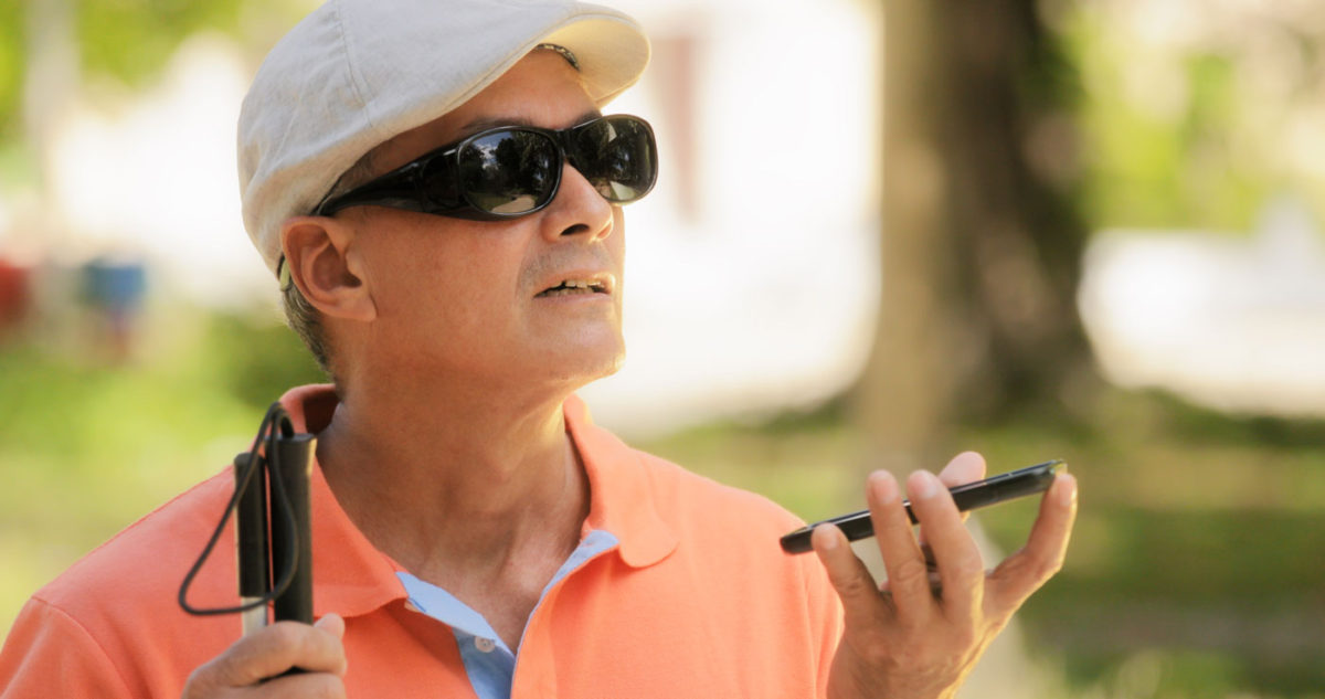 visually impaired man with white cap and sun glasses holds a guide cane and dictates word to his phone which he holds close to his mouth with his left hand